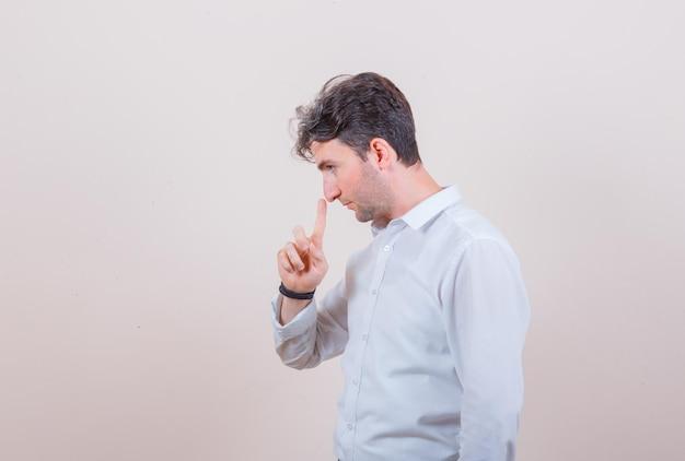 Молодой человек трогает нос пальцем в рубашке и смотрит задумчиво