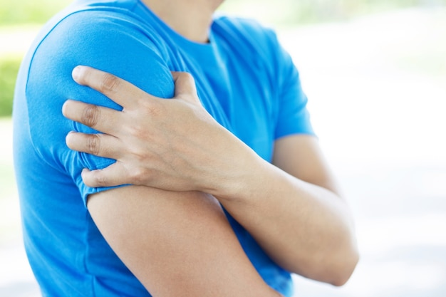 痛みを伴うねじれたまたは壊れた肩に触れる若い男。アスリートトレーニング事故。