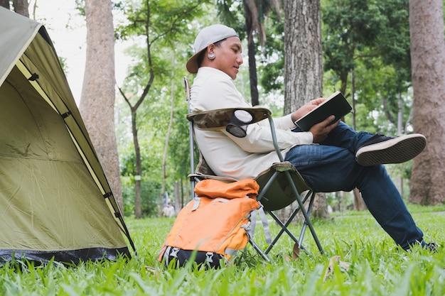 若い男の観光客が椅子に座って、森のキャンプ場でテントの前で本を読んでいます。
