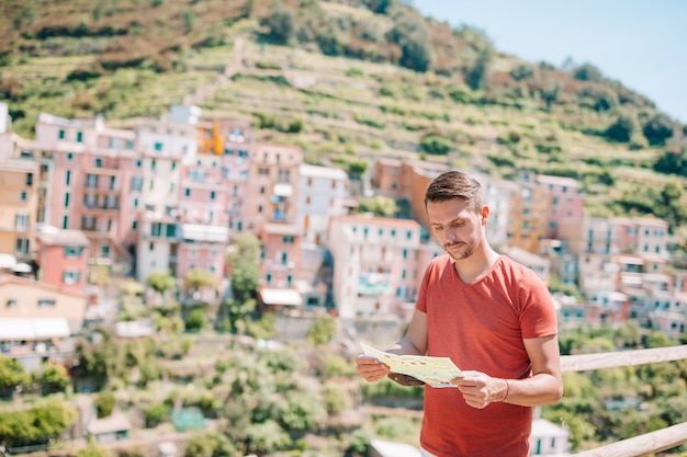 Young man tourist with map in a stunning villag, manarola, cinque terre, liguria, italy