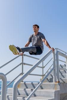 海の近くの屋外で腹筋を訓練する若い男