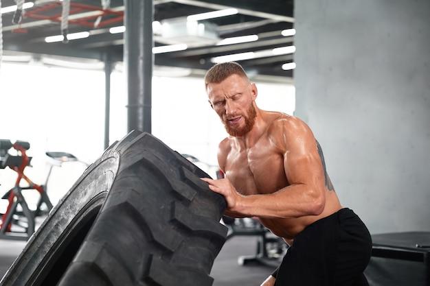 Молодой человек тренируется в тренажерном зале