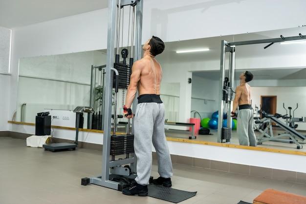 ジムのスポーツ用品でトレーニングをしている若い男
