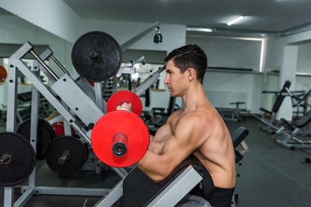 ジムのスポーツ用品で若い男トレーニング