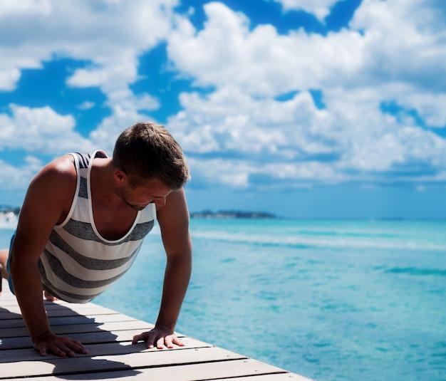 若い男が海でトレーニング。ドックで腕立て伏せをして日焼けする。