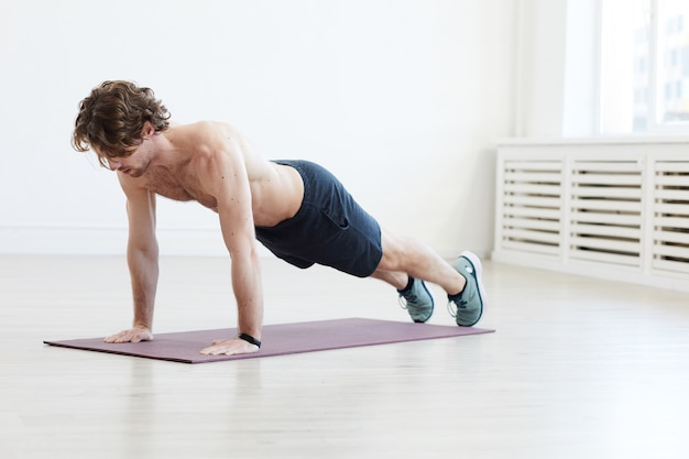 Young man training on exercise mat he doing push-ups during sports training in gym