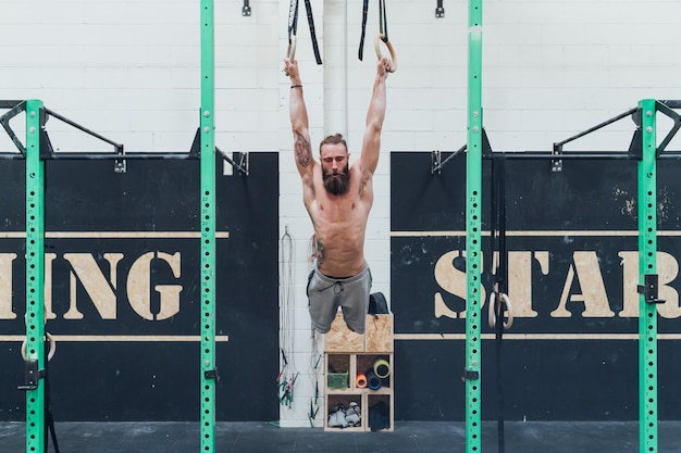 Young man training indoor crossfit gym gymnastic rings