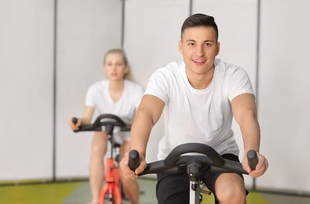Молодой человек тренируется на велосипеде в тренажерном зале