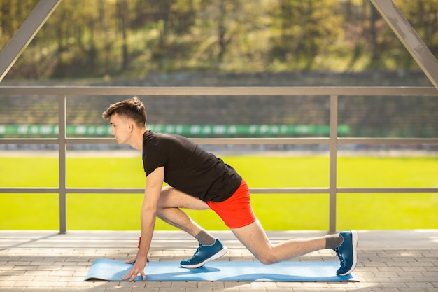 Young man training yoga outdoors. sporty guy makes stretching exercise on a blue yoga mat, on the sports ground.