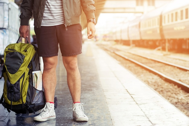 若い男が電車のヒップスターで一人で旅行するショートパンツと靴を履いた足は、駅の地図付きのバックパックを持っています。