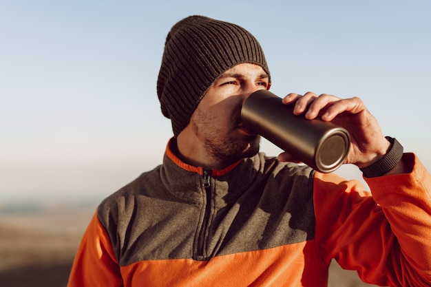Young man traveler drinking from his thermocup while halt on a hike