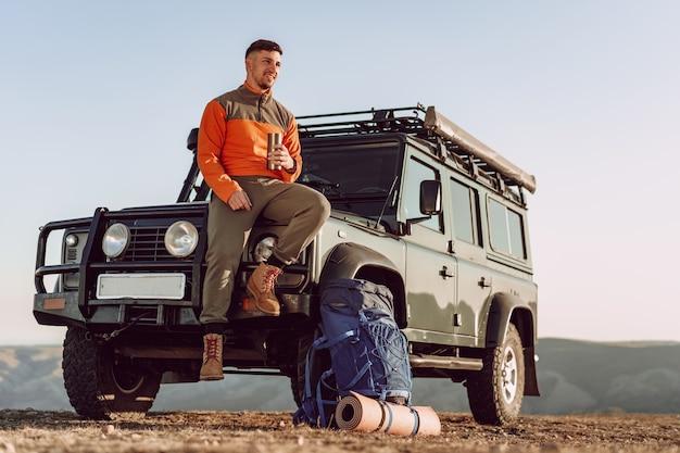ハイキングで停止しながら彼のサーモカップから飲む若い男の旅行者