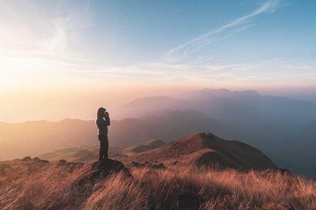 Young man traveler looking beautiful landscape at sunset on mountain