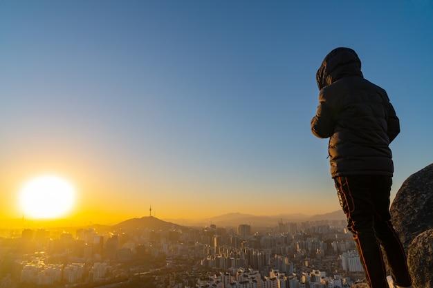 Young man traveler looking at seoul city