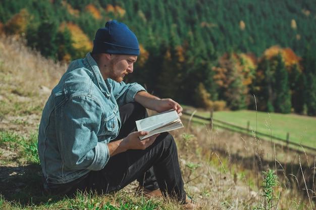 Молодой человек, читающий книгу путешественника, горы на открытом воздухе. летние каникулы и концепция образа жизни.