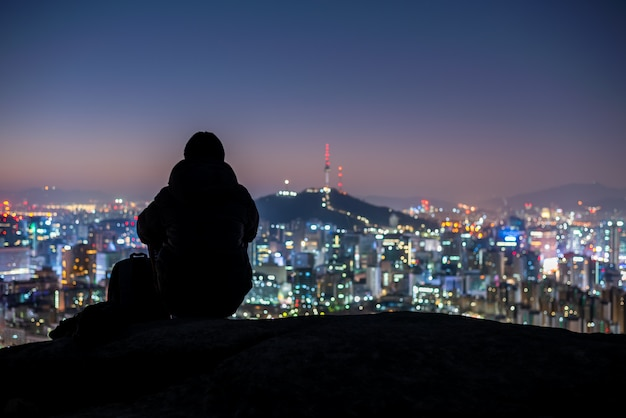 Young man traveler sitting on the rock looking seoul city at night