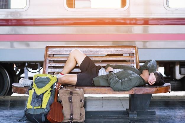 기차를 기다리는 기차역에서 의자에 잠자는 젊은 남자 여행자는 여행, 휴가로 이동