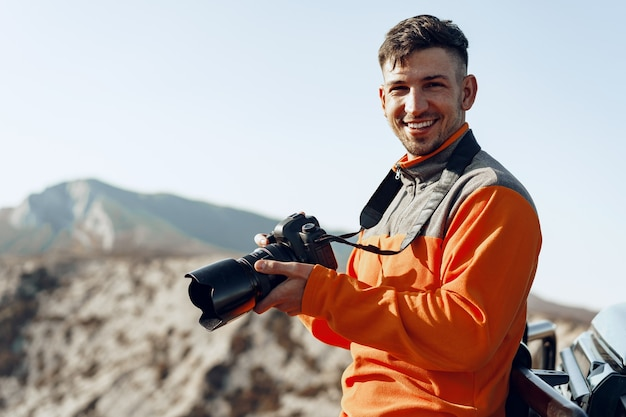 Young man traveler taking photos of mountains landscape with professional camera