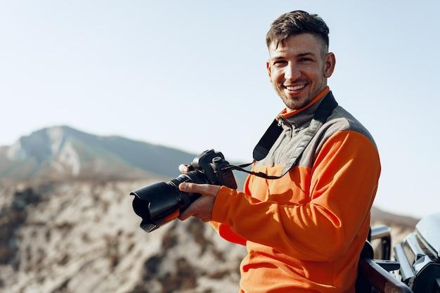 전문 카메라와 함께 산 풍경의 사진을 찍고 젊은 남자 여행자