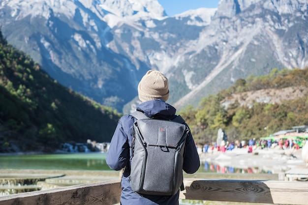 Путешественник молодого человека, путешествующий в долине голубой луны, достопримечательность и популярное место в живописной местности снежной горы нефритового дракона, недалеко от старого города лицзян. лицзян, юньнань, китай. индивидуальная концепция путешествий