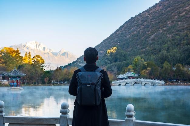 Young man traveler traveling at black dragon pool with jade dragon snow mountain , landmark and popular spot for tourists attractions near lijiang old town. lijiang, yunnan, china