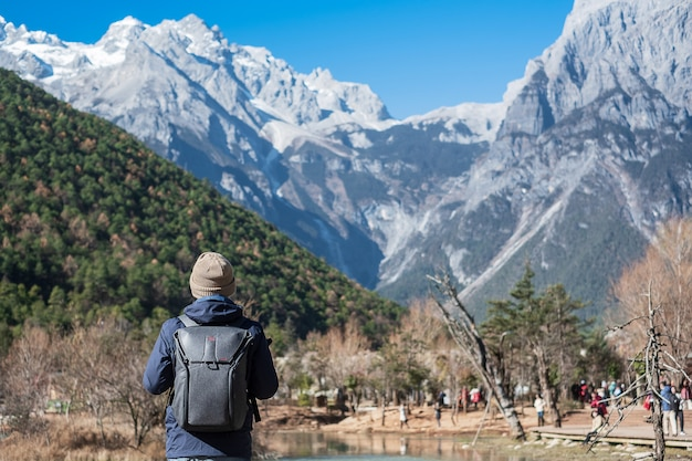 Young man traveler traveling at blue moon valley, landmark and popular spot inside the jade dragon snow mountain scenic area, near lijiang old town. lijiang, yunnan, china. solo travel concept