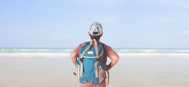 Young man traveler with backpack in the beach