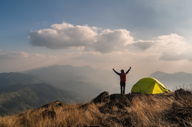 Young man traveler with backpack camping on mountain