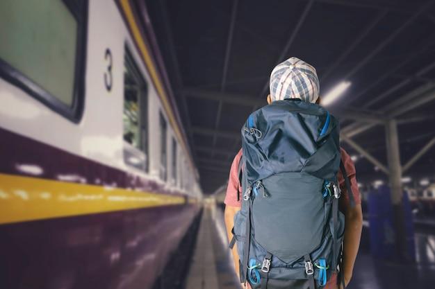 Путешественник молодого человека с рюкзаком в железной дороге, концепцией перемещения.