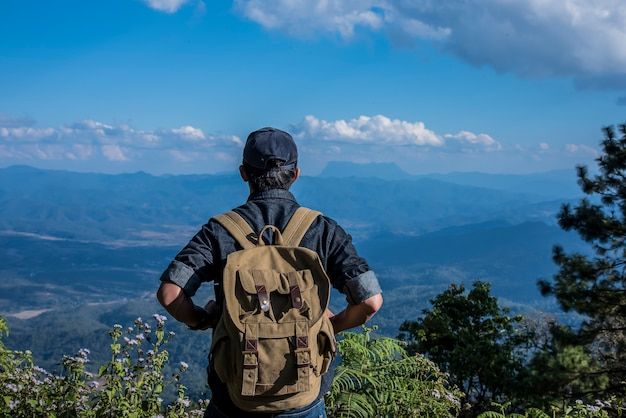 Young man traveler with backpack relaxing outdoor with rocky mountains on background summer vacations and lifestyle hiking concept.