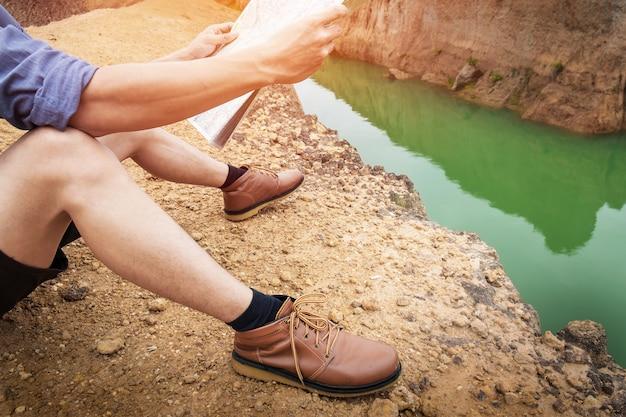 Молодой человек путешественник с рюкзак, расслабляющий на открытом воздухе с скалистые горы на фоне летние каникулы и образ жизни походы концепции.