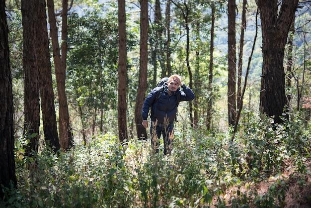 Молодой человек путешественник с рюкзаком в гору, наслаждаясь природой вокруг, концепция путешествия образа жизни.