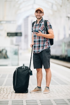 Young man traveler with bag look in phone on train station