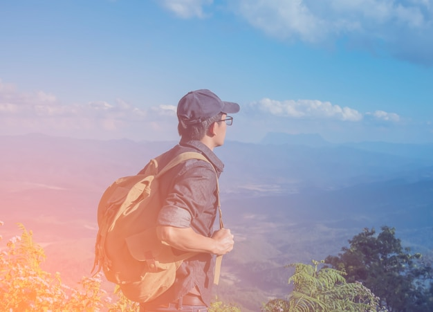 Young man traveler with map backpack relaxing outdoor with rocky mountains on background summer vacations and lifestyle hiking concept