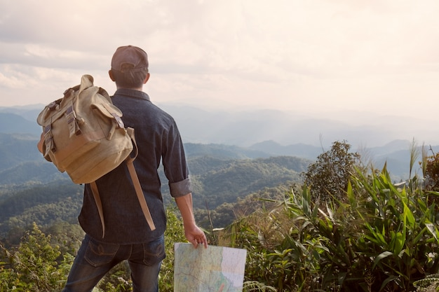 ヤングマントラベラーマップのバックパックで背景にロッキー山脈のある屋外でリラックス夏休みとライフスタイルのハイキングのコンセプト
