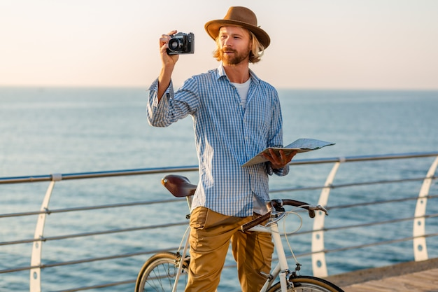 Young man traveling on bicycle by sea on summer vacation by the sea on sunset, holding map sightseeing taking photo on camera