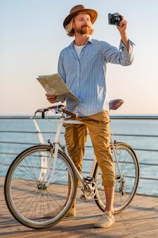 若い男が夕日に海沿いの夏休みに海で自転車で旅行、カメラで地図観光撮影写真を保持
