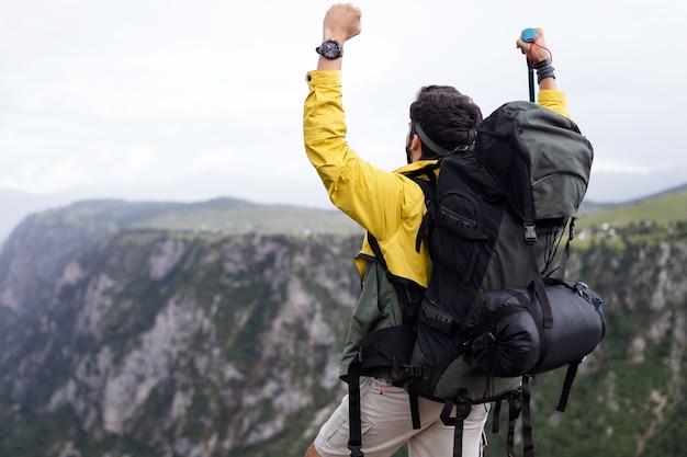 山でバックパックハイキングと一緒に旅行する若い男