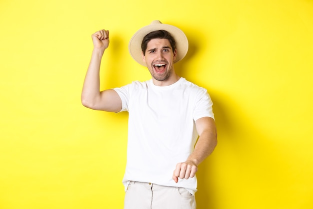 Young man traveller showing rodeo gesture, standing in straw hat and white clothes, standing over yellow wall