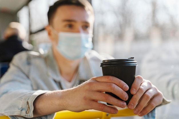 Young man travelling by city bus holding a coffee cup