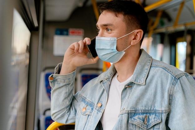Молодой человек путешествует на городском автобусе с помощью смартфона