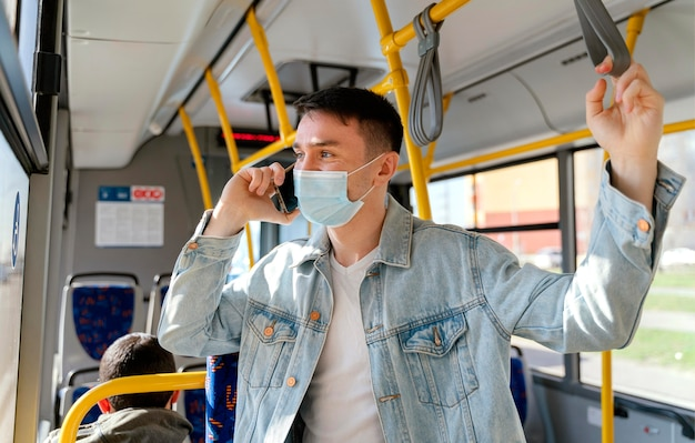 Young man travelling by city bus using smartphone