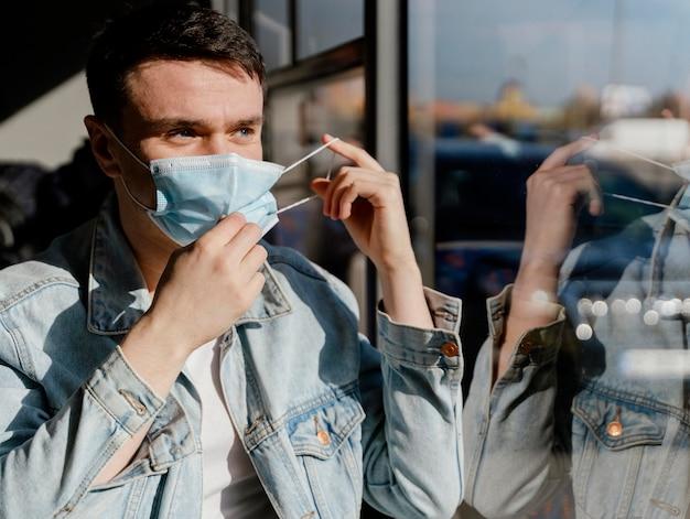 수술 용 마스크를 쓰고 시내 버스로 여행하는 젊은 남자