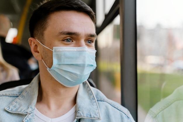 Giovane che viaggia in autobus urbano che indossa la mascherina chirurgica