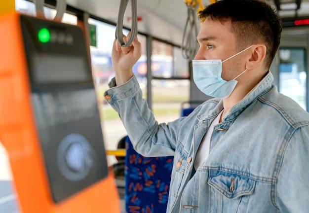 Молодой человек путешествует на городском автобусе в хирургической маске