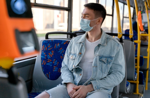 Young man travelling by city bus wearing surgical mask