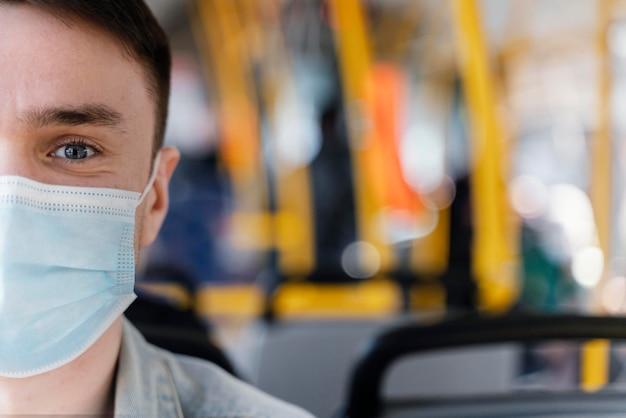 サージカルマスクを身に着けている市バスで旅行している若い男