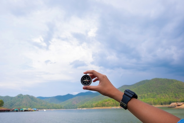 Young man trekker searching direction with a compass enjoy traveling with backpack