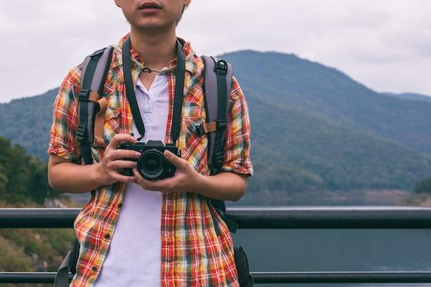 Young man trekker use digital camera take photo enjoy traveling with backpack