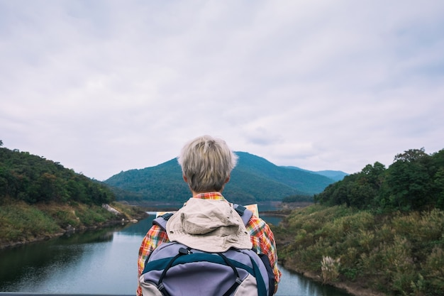 Young man trekker use map and enjoy traveling with backpack, hiking concept